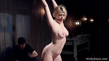 Gagged busty babe in bondage in dungeon