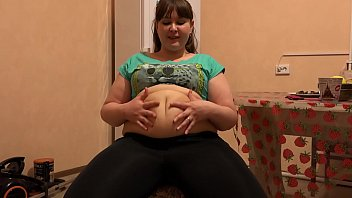 A beautiful bbw in leggings and with a big belly eats and shakes a thick stomach. Home fetish.
