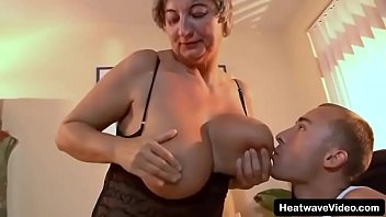 Grandson licks his grandmother's tits then picks up granny to the desk spreading her sexy legs and has intense sex with this old slut