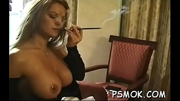 Girl enjoys a cigarette while putting a pecker in her face hole