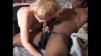 Mature slut rides black cock while sucks white cock