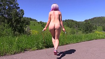 Sexy nudist in a public place jumps on a jump rope outdoors and shakes a big butt. Fetish.