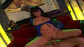 Curvy brunette Asian rides a stud cowgirl style on the sofa