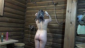 Bottle in the ass and a long dildo in anal. Brunette with a juicy ass masturbates and washes in a sauna.