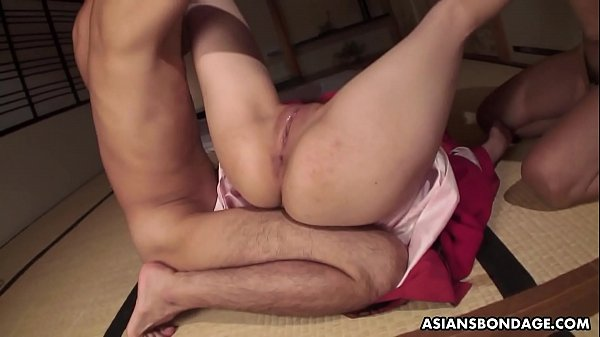 Tied up Asian bimbo sucks two cocks and gets toyed