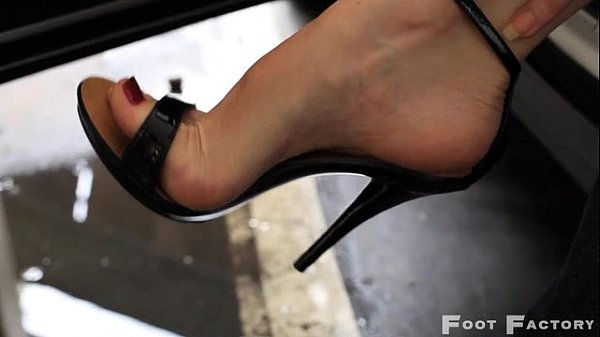 Kelly Space high arched feet in flip flops and high heels parking lot Thumb