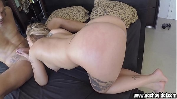 Aris kneels and takes half of Nacho's giant dick down her throat, worshiping his meat and fingering her own asshole
