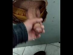 Punhetando o pauzudo no glory hole do banheiro